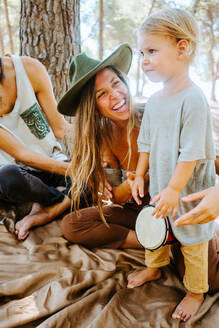 Delighted mother and crop father teaching little kid playing bongo drum while spending time together in woods - ADSF20283
