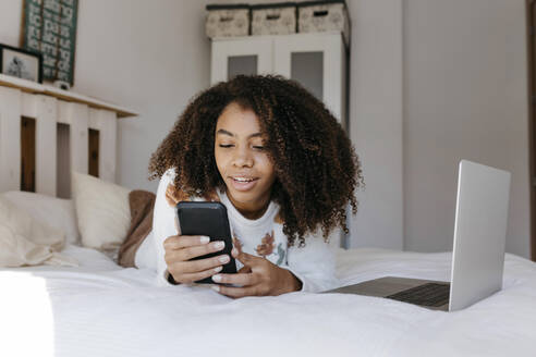 Curly hair woman with laptop using mobile phone while lying on bed at home - TCEF01467
