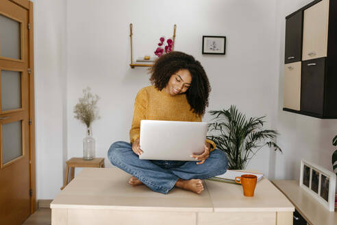 Young woman using laptop while sitting on table at home - TCEF01497