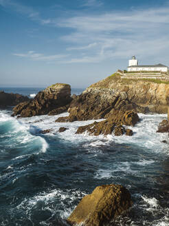 Rough coastline with lighthouse in background, Asturias, Spain - JMPF00851