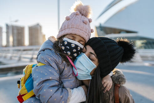 Mother and daughter wearing knit hat and face mask hugging while standing outdoors - EGAF01527