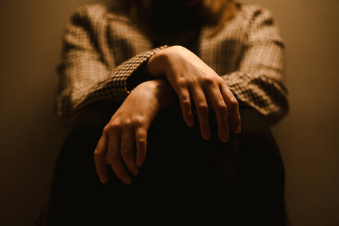 Selective focus of hands of crop anonymous exhausted depressive unhappy woman in checkered coat sitting in dark studio - ADSF20363