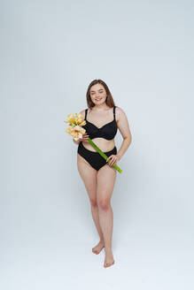 Young woman wearing black bikini holding flowers standing against white background - OIPF00099