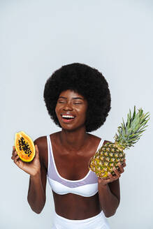 Afro-American woman wearing lingerie holding papaya and pineapple laughing against white background - OIPF00117
