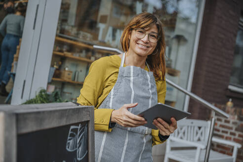 Smiling female entrepreneur holding digital tablet while standing against retail shop - MFF06892