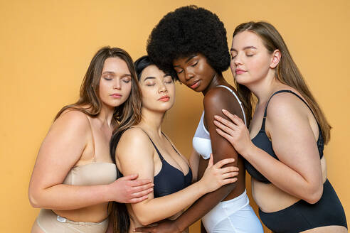 Multi-ethnic group of female models in lingerie with eyes closed embracing each other by yellow background - OIPF00122