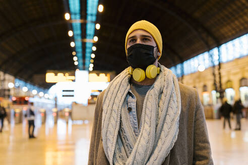 Man with face mask and headphones looking away while standing at station - EGAF01567