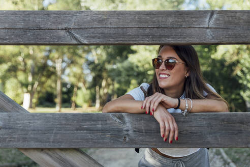 Smiling young woman wearing sunglasses leaning on wooden fence in forest - JRVF00173
