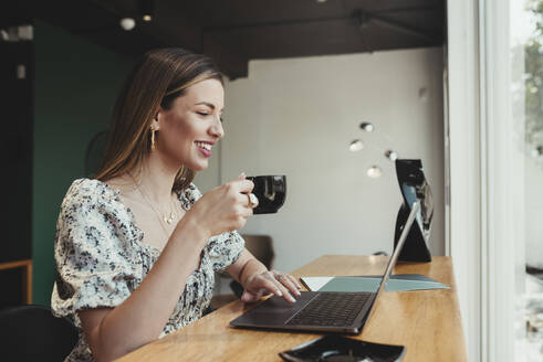 Businesswoman holding coffee cup while working over laptop on table in restaurant - DSIF00284