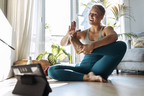 Smiling woman doing yoga while learning through digital tablet at home - JSRF01272