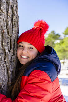 Young woman wearing red knit hat smiling while hugging tree standing in forest - DLTSF01562