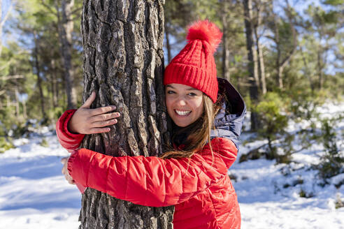 Happy man wearing knit hat while hugging tree in forest - DLTSF01568