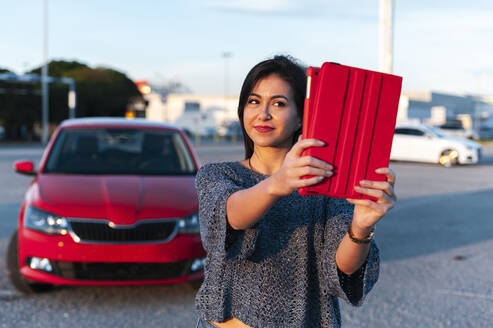 Beautiful young woman taking selfie with digital tablet against red car on sunny day - JMPF00872