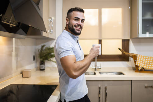 Smiling muscular man holding coffee cup while leaning at kitchen counter at home - MIMFF00515