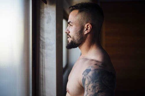 Shirtless man with tattoo looking through window at home - MIMFF00527