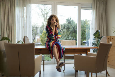 Young woman drinking coffee while sitting on table in living room - AXHF00121