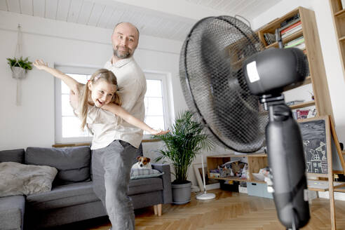 Father playing with cheerful daughter in front of electric fan at home - KMKF01479