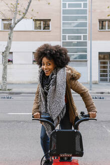 Cheerful Afro woman sitting on bicycle against building on street - XLGF01049