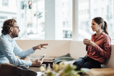 Female entrepreneur having coffee while discussing with male colleague at coffee shop - JOSEF03187