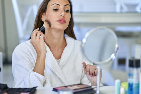 Woman applying blusher while looking in mirror at home - KIJF03522