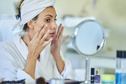 Woman applying cream on her face in front of mirror home - KIJF03531