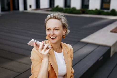 Happy female entrepreneur talking through smart phone while sitting on floorboard - KMKF01492