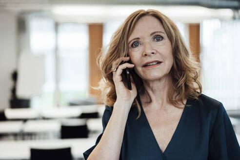 Businesswoman talking on smart phone in office - JOSEF03274