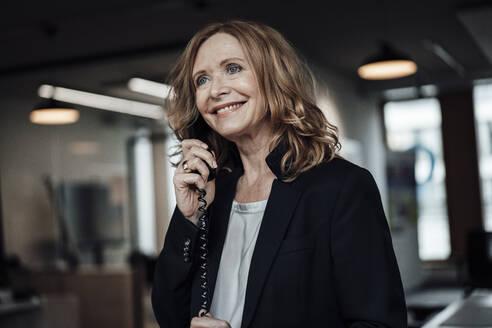 Beautiful businesswoman talking on telephone in office - JOSEF03334