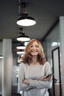 Smiling senior businesswoman with smart phone in illuminated office - JOSEF03340