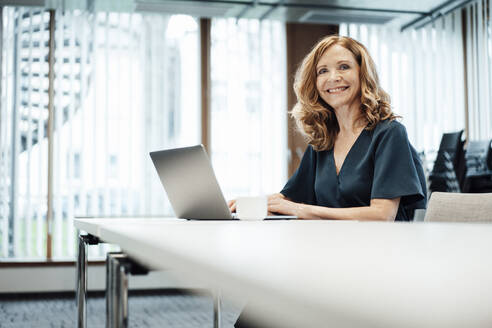 Smiling businesswoman with laptop at conference table in board room at office - JOSEF03367
