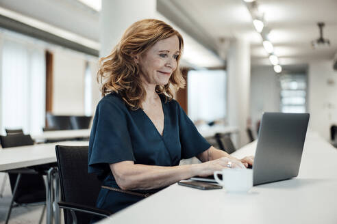 Smiling businesswoman working on laptop at conference table in board room - JOSEF03373