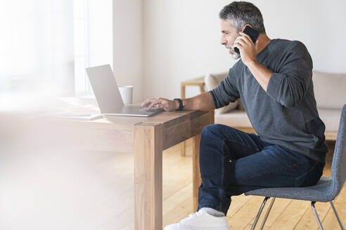 Businessman talking on mobile phone while using laptop sitting at home - SBOF02600