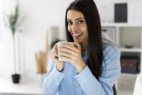 Smiling businesswoman drinking coffee while sitting at office - GIOF10905