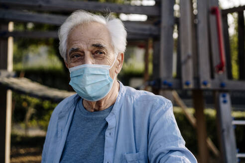Senior man wearing protective face mask staring while standing at park - GUSF05153