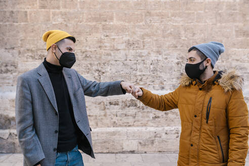 Young friends wearing protective face mask giving fist bump while standing against wall - EGAF01625