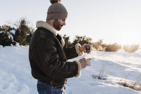 Young man with jacket pouring coffee in cup through thermos while standing on snow - EBBF02391