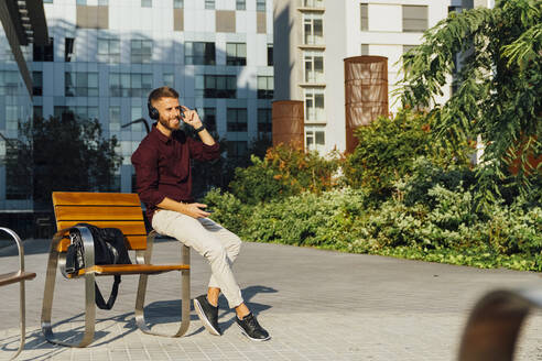 Smiling businessman with mobile phone adjusting headphones while sitting on bench in city - BOYF01662