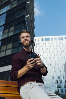 Businessman wearing headphones using mobile phone while sitting in city - BOYF01665
