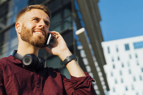 Smiling businessman wearing headphones talking on mobile phone while standing in city - BOYF01668