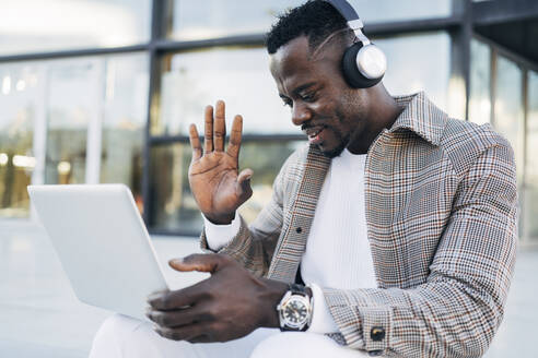 Man wearing headphones gesturing while video calling on laptop - MPPF01430