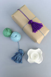 Studio shot of balls of wool and wrapped gift with wool tassel - GISF00754