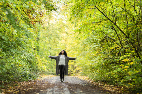Carefree woman with arms outstretched running on footpath in forest - AKLF00001