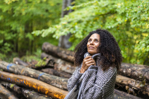 Thoughtful woman looking up while sitting in forest - AKLF00007