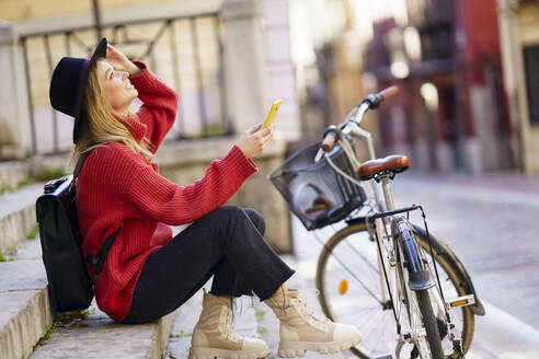 Woman with mobile phone looking up while sitting by bicycle on steps - JSMF01950