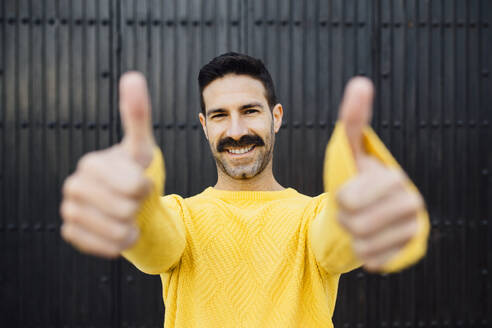 Happy man showing thumbs up while standing against against black wall - MIMFF00552