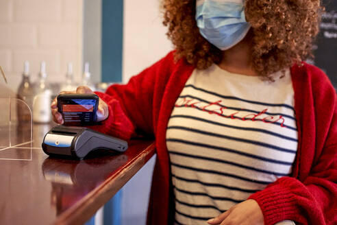 Afro woman wearing sanitary mask while making contactless payment through mobile phone at cafe - VEGF03689