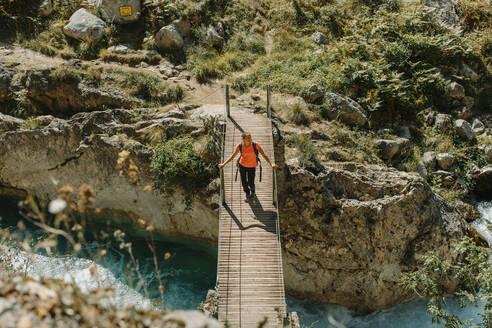 Woman walking on bridge while exploring Cares Trail in Picos De Europe National Park, Asturias, Spain - DMGF00475