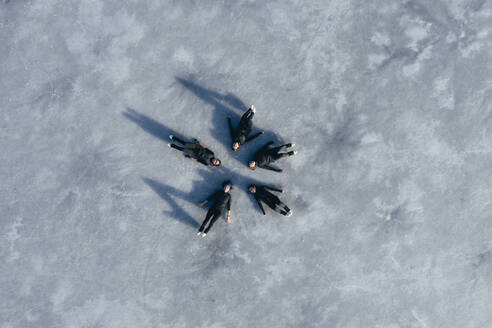 Aerial view of group of female ice-skaters lying together on surface of frozen lake - RSGF00543