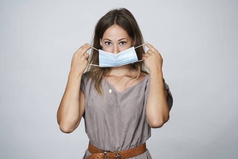 Young woman wearing protective face mask during pandemic against gray background - AKLF00017