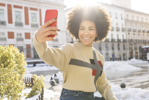 Afro woman smiling while taking selfie through mobile phone sitting in city - JCCMF01069